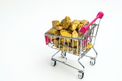 Pile of gold nuggets or gold ore in shopping cart or supermarket trolley on white background, precious stone or lump of golden. Stone, financial and business stock image