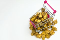 Pile of gold nuggets or gold ore in shopping cart or supermarket trolley on white background, precious stone or lump of golden. Stone, financial and business royalty free stock images