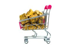 Pile of gold nuggets or gold ore in shopping cart or supermarket trolley on white background, precious stone or lump of golden. Stone, financial and business royalty free stock image