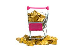 Pile of gold nuggets or gold ore in shopping cart or supermarket trolley on white background, precious stone or lump of golden. Stone, financial and business stock photo