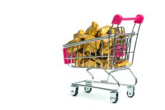 Pile of gold nuggets or gold ore in shopping cart or supermarket trolley on white background, precious stone or lump of golden. Stone, financial and business stock images
