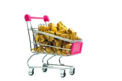 Pile of gold nuggets or gold ore in shopping cart or supermarket trolley on white background, precious stone or lump of golden. Pile of gold nuggets or gold ore royalty free stock photography
