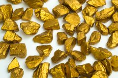 A pile of gold nuggets or gold ore on white background, precious stone or lump of golden stone, financial and business concept. Idea stock photography