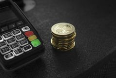 A pile of gold Ripple Crypto currency coins and POS terminal. Ripples Cryptocurrency. E-commerce, business, finance. Concept, banking and payment royalty free stock images