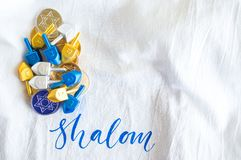 Pile of gold and silver Hanukkah coins with tiny dreidels on a white linen cloth Royalty Free Stock Photo
