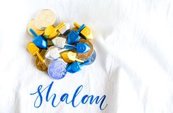 Pile of gold and silver Hanukkah coins with tiny dreidels on a white linen cloth Stock Photos