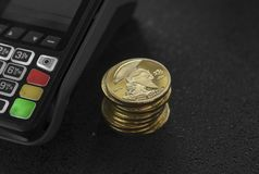 A pile of gold Titan Crypto currency coins and POS terminal. Titans Cryptocurrency. E-commerce, business, finance. Concept, banking and payment stock images