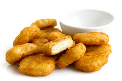 Pile of golden deep-fried battered chicken nuggets with empty bo Stock Image