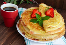 Pile of golden pancakes with strawberries and strawberry jam, decorative sprig of mint. Royalty Free Stock Photography