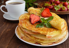 Pile of golden pancakes with strawberries and strawberry jam, decorative sprig of mint and cup of tea. Royalty Free Stock Photos