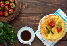 Pile of golden pancakes with strawberries and strawberry jam, decorative sprig of mint. Royalty Free Stock Photos