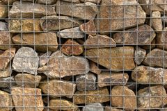 A pile of granite rocks in a metal cage used for flood prevention, mostly brown in colour royalty free stock images