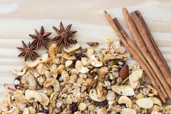 The Pile of granola cereal and cinnamon sticks on the wood backgroun Royalty Free Stock Images
