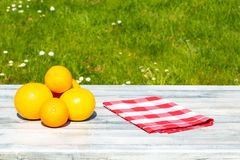 A pile of grapefruits and a red white checkered empty tablecloth. On rustic bright table with natural green background. Concept Health Royalty Free Stock Photography