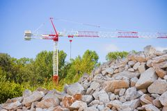 Pile of gravel, stones and pebbles of different sizes against a tower crane.  stock photography