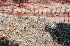Pile of gravel on the street construction site with orange safety net or fence close up.  stock images