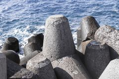 Pile of gray breakwaters cement coast guard against the sea large stone triangles powerful weather-beaten royalty free stock images