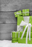 Pile of green Christmas presents, with snow on grey  Royalty Free Stock Image