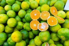 A pile of green mandarins. A pile of green and ripen mandarins which some of them sliced into two pieces to show their inside Stock Image