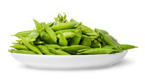 Pile of green peas in pods on white plate. Isolated on white background Royalty Free Stock Photography