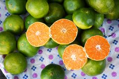 A pile of green mandarins. A pile of green and ripen mandarins which some of them sliced into two pieces to show their inside Stock Photos