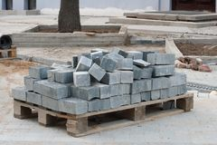 Pile of  grey granite pavement bricks on a palette are ready to be laid in the sidewalk Royalty Free Stock Photography