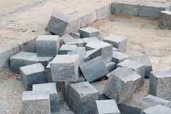 Pile of  grey granite pavement bricks are ready to be laid in the sidewalk Stock Photography