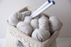 Pile of grey yarns. Grey alpaca wool yarns in a basket with big knitting needles, on a white shabby chic table Royalty Free Stock Image