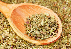 Pile of ground dried Basil (Sweet Basil) as background with wooden spoon. Used as a spice in culinary herb all over the world. Stock Photos