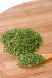 Pile of grounded parsley and on wooden spoon Royalty Free Stock Photography