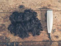 Pile of hair and clippers on a wooden table Stock Images