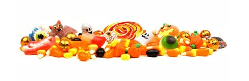 Pile of Halloween candy over white. Long pile of colorful Halloween candy and sweets over a white background Stock Photo