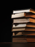 Pile of hardcover books in a shadowy room Stock Photography