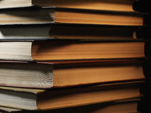 Pile of hardcover books in a shadowy room. Pile of hardcover books stacked on top of one another in a shadowy room on a wooden desk with copyspace in the Stock Photos