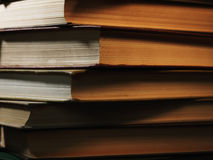 Pile of hardcover books in a shadowy room Royalty Free Stock Image