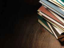 Pile of hardcover books in a shadowy room Royalty Free Stock Photography