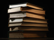 Pile of hardcover books in a shadowy room Royalty Free Stock Images