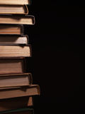 Pile of hardcover books in a shadowy room Royalty Free Stock Photo
