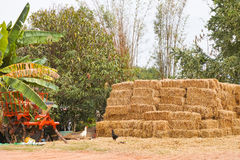 Pile of hay bales. Beside harvesting machine stock photos