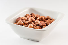 Pile of hazelnuts in a ceramic bowl. Pile of fried hazelnuts in a white ceramic bowl isolated on a white background Royalty Free Stock Images