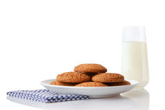 Pile of homemade oatmeal cookies on white ceramic plate on blue napkin and glass of milk Royalty Free Stock Images