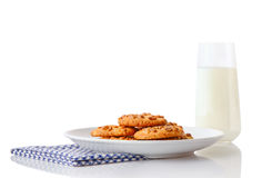 Pile of homemade peanut butter cookies on white ceramic plate on blue napkin and glass of milk Stock Photos