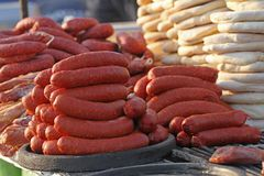 Pile of homemade raw sausages and baked bread - purlenka. Raw sausages and bread prepared for grill. Fast food outside. stock photo