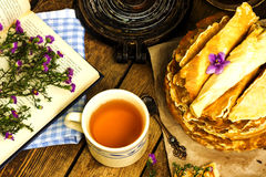 Pile of homemade wafers with tea, book and flowers Royalty Free Stock Image