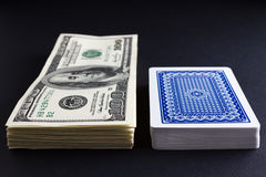 Deck of cards and pile of money Stock Photography