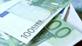 Pile of Hundred Euro Banknotes on a Table. A pile of hundred euro banknotes on a table. Close-up dolly shot Stock Photo