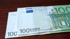 Pile of Hundred Euro Banknotes on a Table. A pile of hundred euro banknotes on a table. Close-up shot Stock Photo