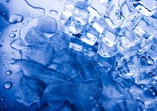 Pile of ice cubes. Pile of ice cubes, some melting on a surface and with blue coloration. Impurities, such as air,  produce the bluish white color Stock Photo