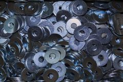 Pile of industrial galvanized steel washers. Lots of reflecting industrial galvanized steel washers on a pile Royalty Free Stock Photo