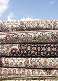 Persian carpet. A pile of Iranian carpets and rugs in a nice design in a nice blue sky background Royalty Free Stock Images